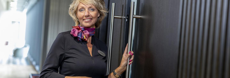 Gastvrouw in uniform houdt de hendel van een grote deur vast.