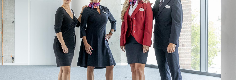 Drie vrouwelijke receptionisten en een gastheer staan geposeerd voor de camera in hun uniformen.