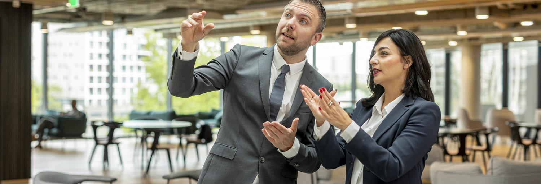 Man en vrouw in zakelijke kleding overleggen met elkaar en wijzen naar een bord.
