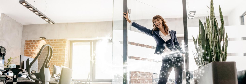 Vrouw in zakelijke kleding rolt op rollerskates binnen op kantoor.