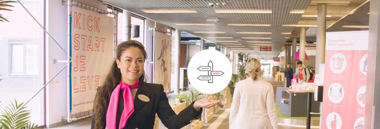 Vrouw in uniform wijst een icoontje aan waarop een paal met wegwijzers is afgebeeld.