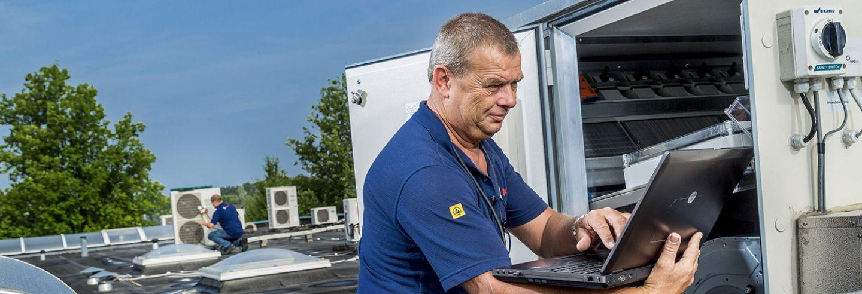 Man aan het werk met zijn laptop bij een ventilatie installatie op het dak.