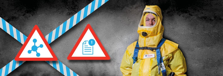 een medewerker van Gom Specialistische reiniging in een geel en geheel afgesloten beschermend pak staat voor een grijze achtergrond met daarnaast waarschuwingsborden en afzetlinten