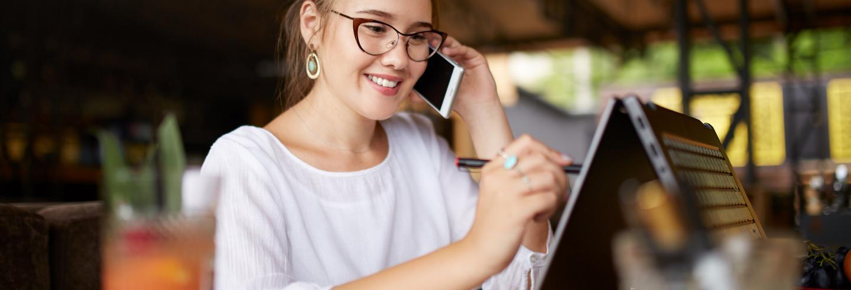 Vrouw is aan het telefoneren en tevens aan het werk achter haar laptop