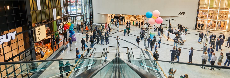 Een overzichtfoto van een ruime moderne winkelruimte met daarin winkelend publiek