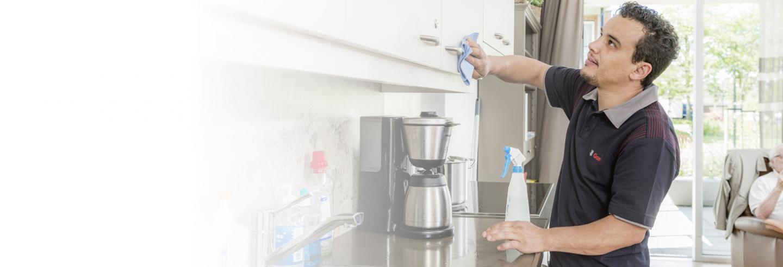 een medewerker van Gom in een donkerblauwe bedrijfspolo maakt met een doekje het deurtje van een keukenkastje van een bewoner van een verzorgingstehuis schoon