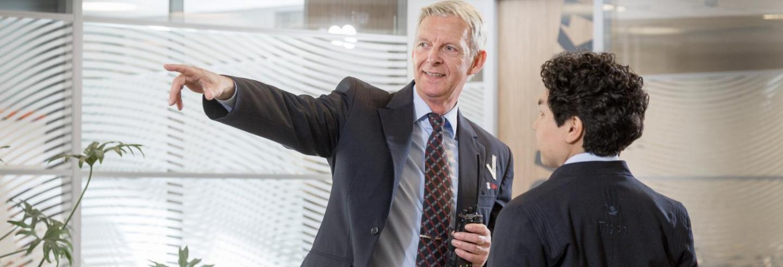 Mannelijke beveiliger in uniform helpt mannelijke bezoeker opweg met de juiste wandelroute naar zijn bestemming binnen het kantoorpand.
