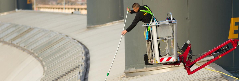 een medewerker van Degenaar is in een bakje van een hoogwerker met een telescoopstok het dak aan het schoonmaken