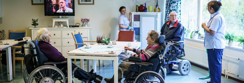 drie ouderen in een rolstoel zitten om een tafel, 2 medewerkers van Gom Zorg doen de schoonmaak