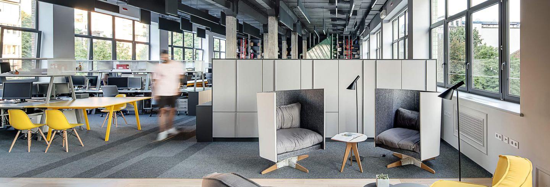 Moderne open kantoorverdieping met ramen aan beide zijden en moderne kantoormeubelen met een accent geel