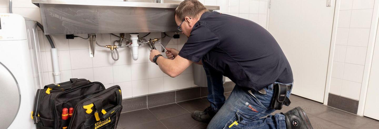 Mannelijke loodgieter die werkzaamheden uitvoert aan de leidingen.