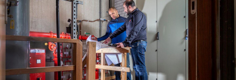 Twee mannelijke Breijer medewerkers spreken plannen door in werkruimte