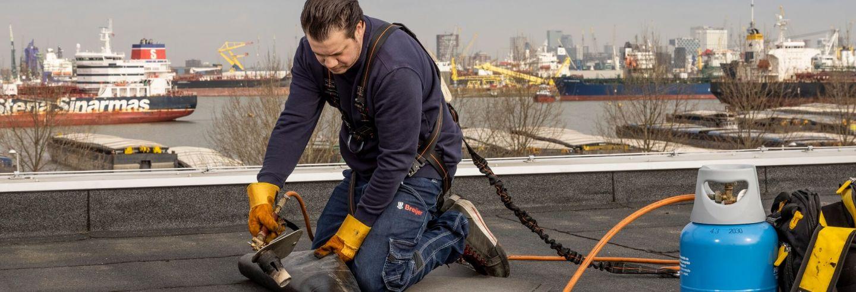 Mannelijke dakbedekker bezig om het dak te bedekken.