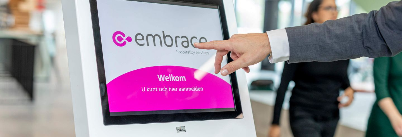 Hand reikt uit naar aanmeldpilaar waarop het logo van Embrace staat vertoond.