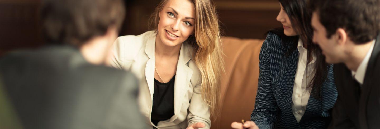 Een viertal collega's die in een informele zetting (bank en lage tafel) met elkaar in overleg zijn.