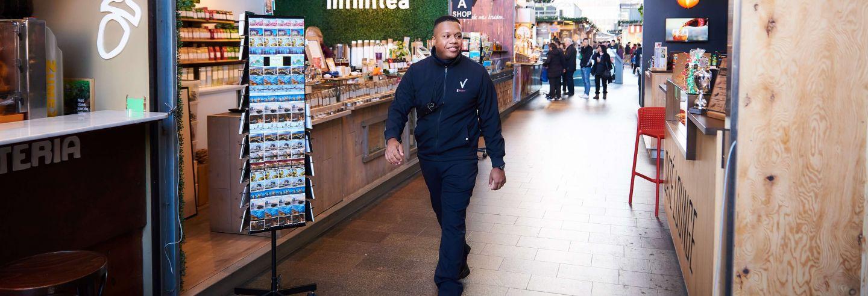 Een retailbeveiliger loopt door de winkelstraat.