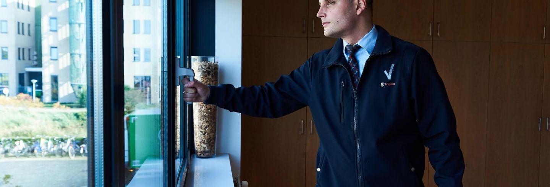 Mobiele surveillance controleert tijdens een sluitronde een raam op veiligheid.