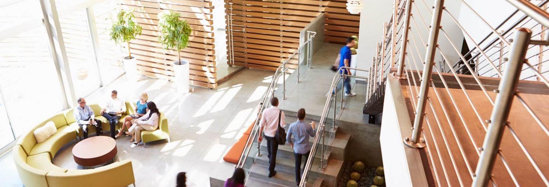 Medewerker in een ruime en moderne hal van een kantoorgebouw. In deze hal staat ook een halfronde gele bank en is een trap te zien die mensen nemen om naar boven te gaan.