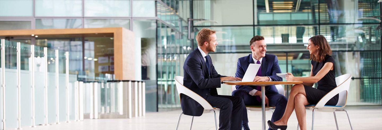 Drie collega's in een informeel overleg aan een tafel in een centrale ruimte van een kantoor.