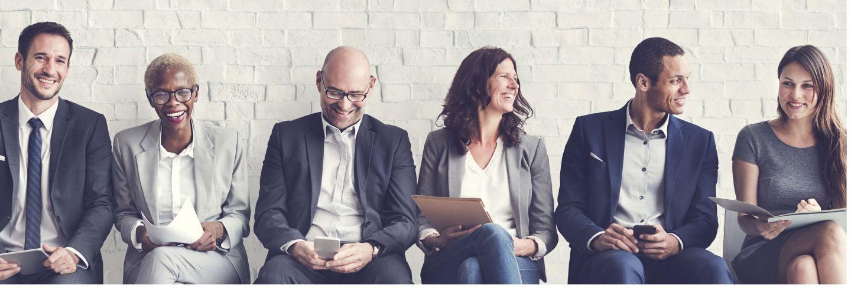 Groep interimmanagers zittend op een rij voor een muur vrolijk lachend en met elkaar in gesprek