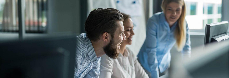 drie projectmanagers met elkaar in gesprek aan bureau kijkend naar beeldscherm.