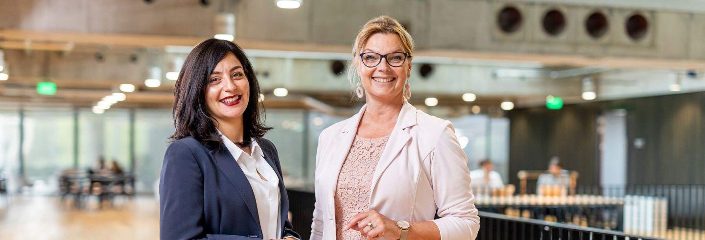 Twee vrouwen in zakelijke kleding staan geposeerd voor de camera in een lichte ruimte.