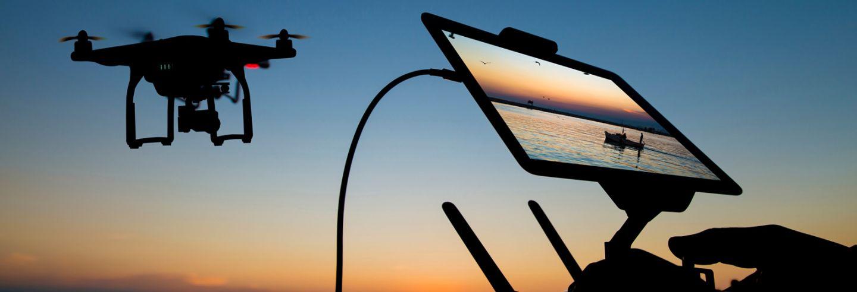 Bij zonsondergang wordt een drone bestuurd door een persoon die de beelden ziet op een schermpje.