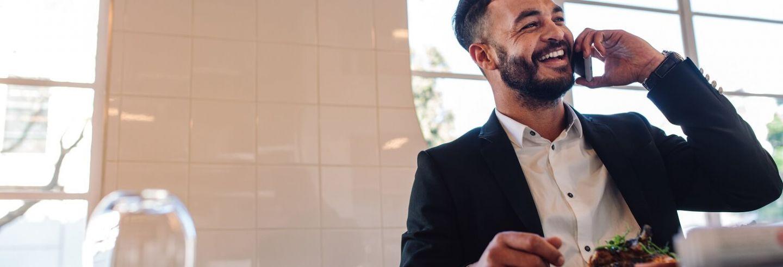 Lachende man aan het telefoneren met een bord met eten voor zich