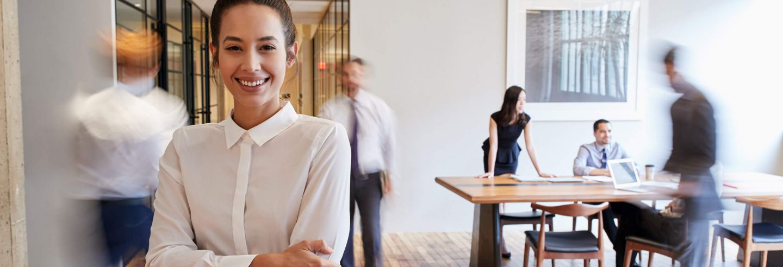 Vrouw staat middenin kantoorruimte waar verschillende collega's langslopen en aan het werk zijn.