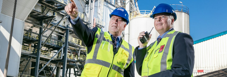 Een beveiligingsmedewerker die een collega met portofoon op een industrieterrein instructie geeft.