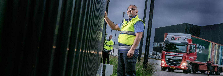 Beveiliger controleert samen met een collega het hekwerk op een bedrijventerrein