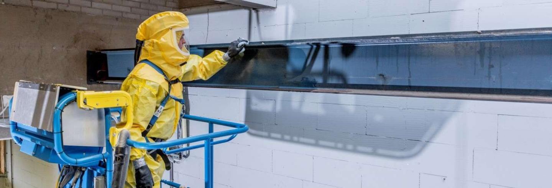 Medewerker in geel beveiligingspak doet reinigingswerk bij een raam.