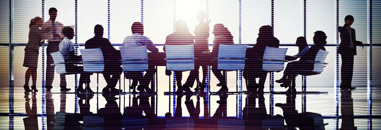 Een groep zit aan een vergadertafel in zakelijke kleding.