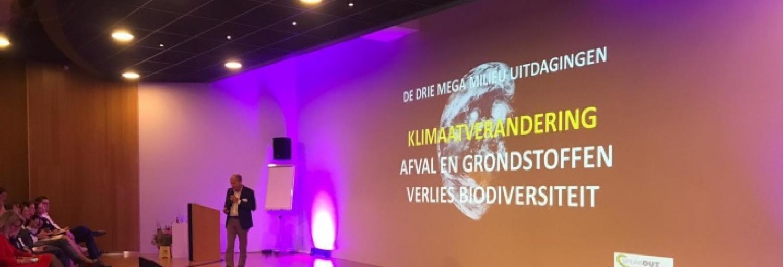 Afbeelding van het podium met spreker en videopresentatie op achtergrond